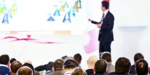 Male Presenter using a slideshow to present to a large audience of business people