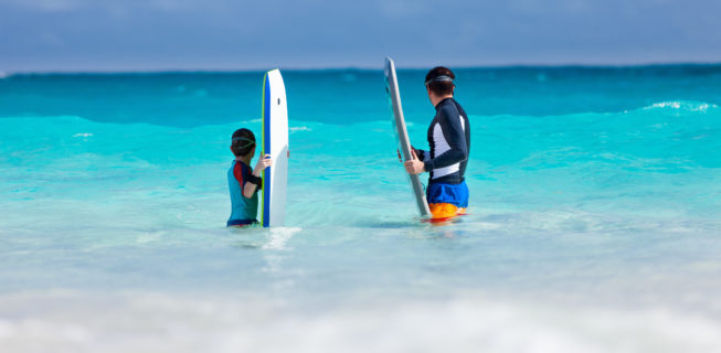 father and son bodyboarding and waiting for a wave