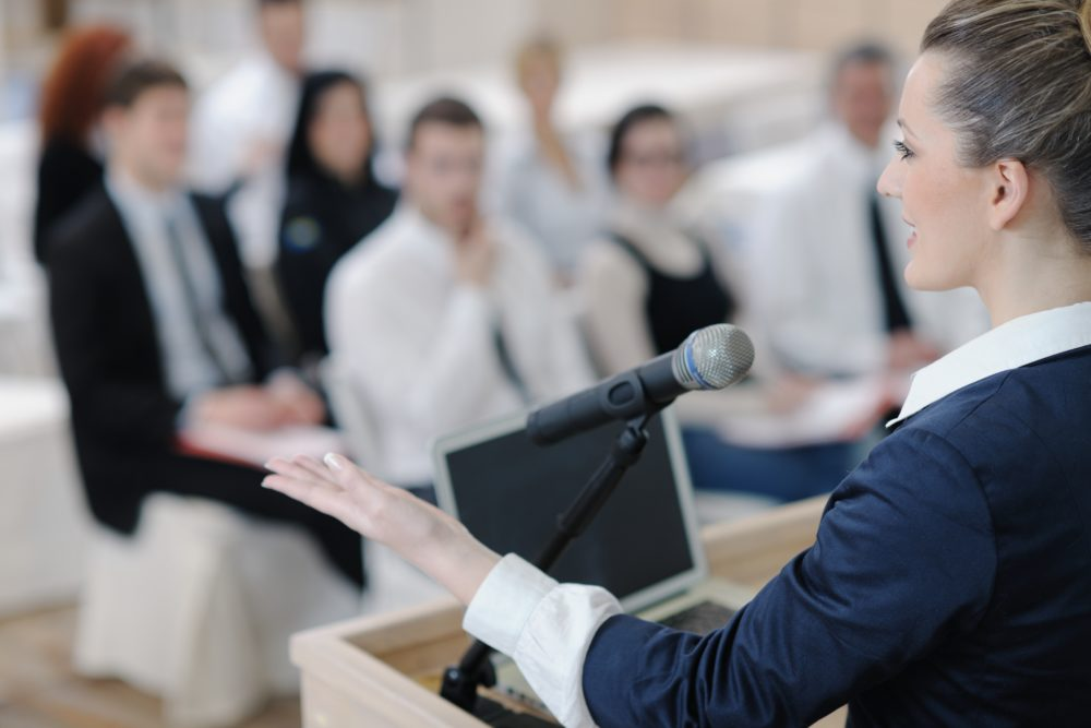 Business Woman presenting to a small audience of employees