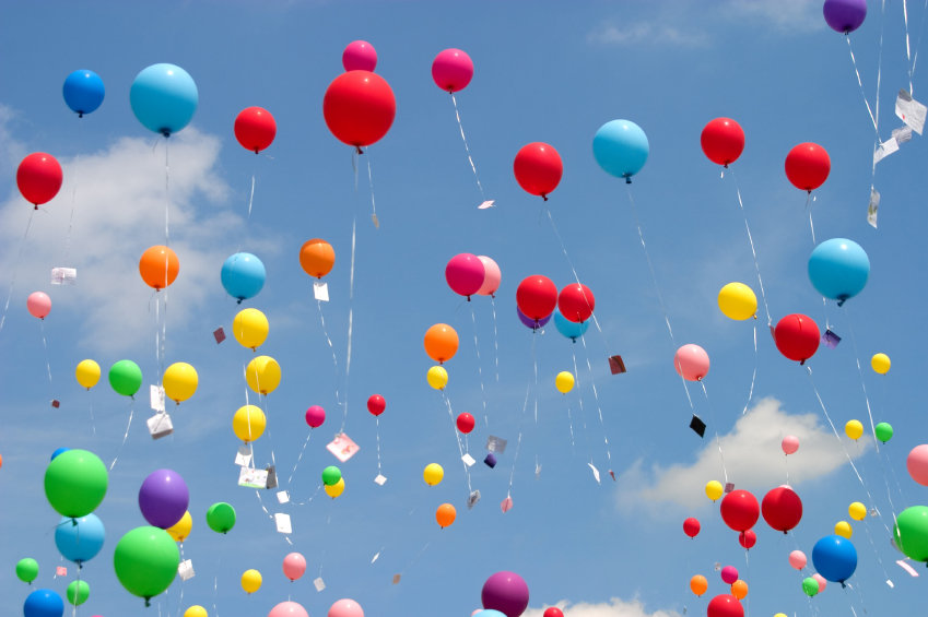 balloons with notes attached flying into the sky