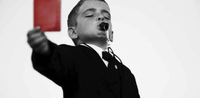 boy wearing a suit with a whistle showing a red card