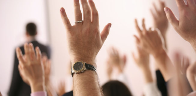 raised hands asking questions during a presentation