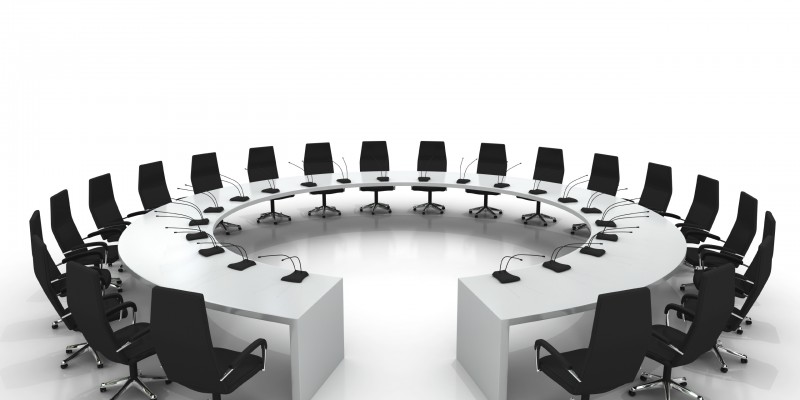 circular conference table with chairs and microphones