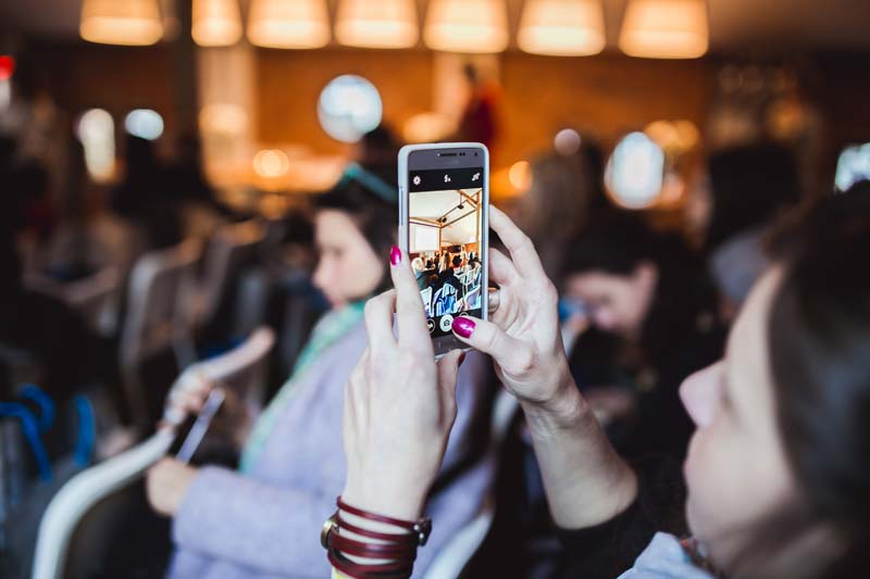 girl taking photo with phone at presentation
