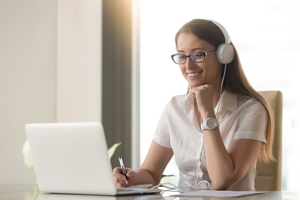 Woman with headphones on laptop presenting online