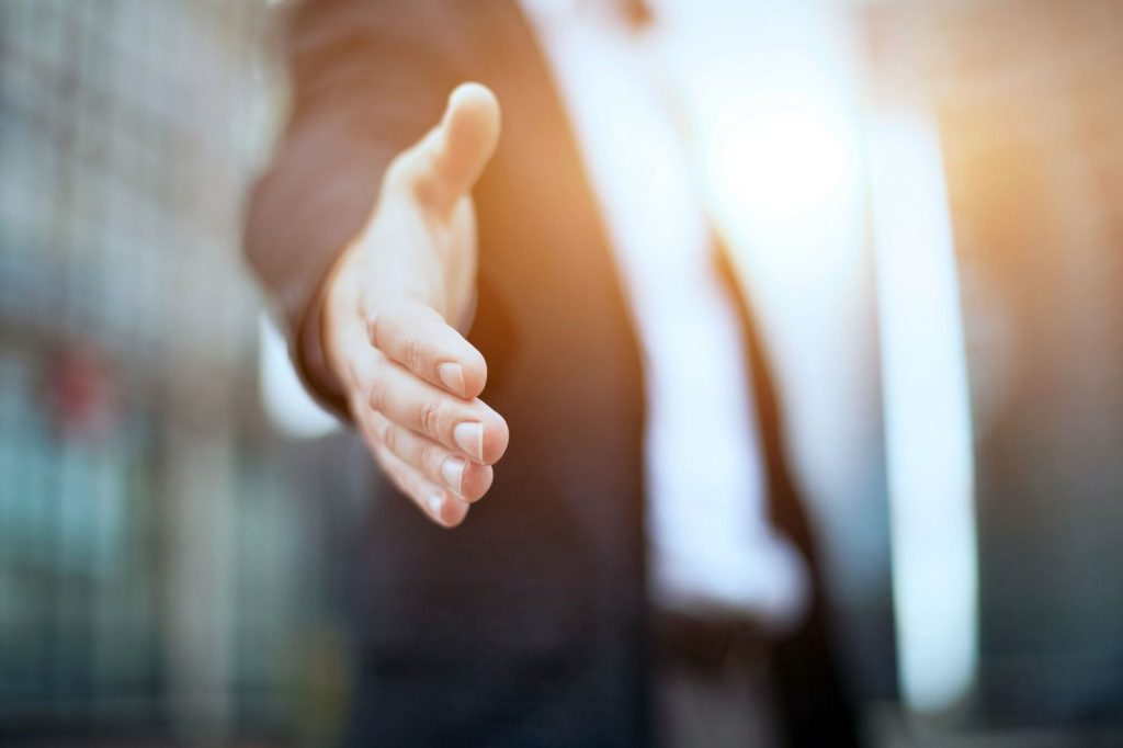Shaking hands to meet and greet your audience is a technqiue that can improve your presentation skills
